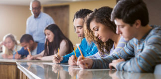 Group of students taking exam in class