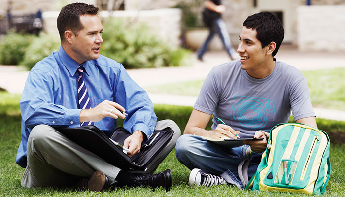 Student talking with teacher on the grass