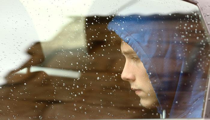 Sad boy inside car