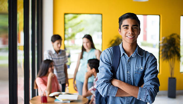 Confident boy standing in front of students