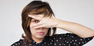 Girl peeking through her hand