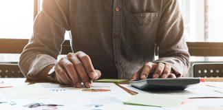 closeup of male using calculator | how to make a budget