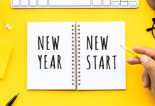 "top down view of yellow desk with note pad saying ""new year new start"" 