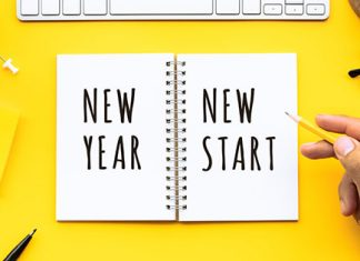 yellow desk with notepad saying new year new start | how to achieve goals