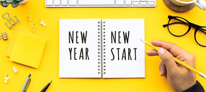 open notebook on yellow desk says new year, new start