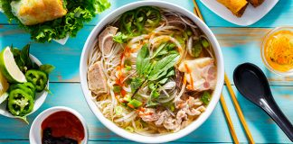 bowl of pho with toppings, sauces and appetizers on the side | simple pho recipe