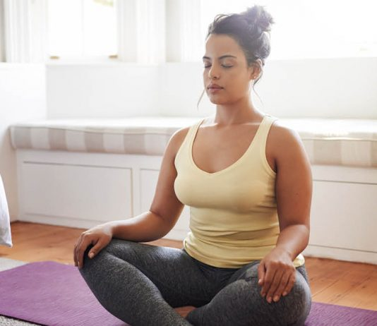 Student advocate: young woman meditating in bedroom