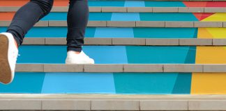 low angle of person climbing colorful stairs