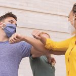 diverse group of friends greeting each other with an elbow bump and wearing masks | social support mental health