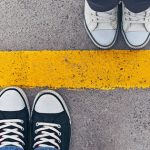 topview of two people's sneakers meeting at a yellow line   setting healthy boundaries