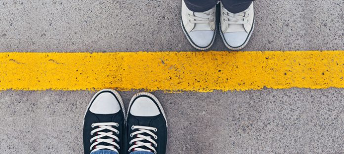 topview of two people's sneakers meeting at a yellow line | setting healthy boundaries