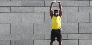 Black male athlete stretching outdoors | barre workout video
