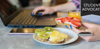 Student advocate: Female hand reaching for healthy snack while working on laptop