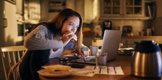 Girl eating in front of computer