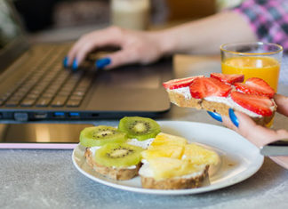 Female hand reaching for healthy snack while working on laptop