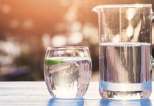 drinking glass and pitcher of water on picnic table