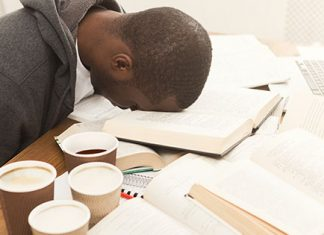 Guy with head on books surrounded by coffee