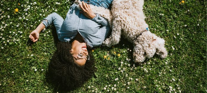Girl with dog laying in grass