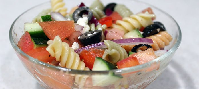 prepared greek pasta salad in glass bowl