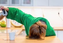woman with head on kitchen counter, pouring coffee and missing mug | causes of feeling tired all the time