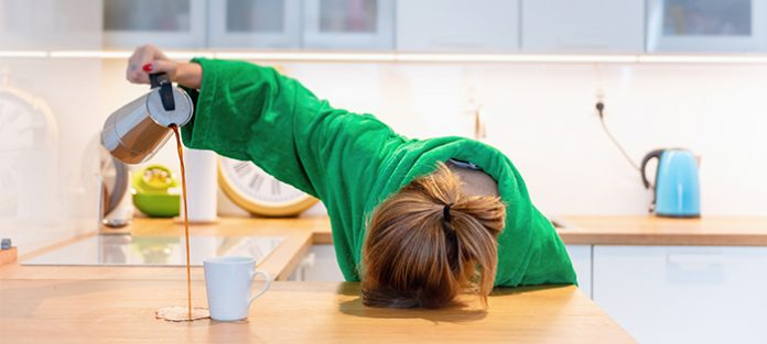 woman with head on kitchen counter, pouring coffee and missing mug   causes of feeling tired all the time