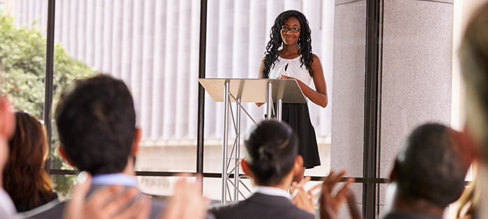 young woman at podium in front of audience