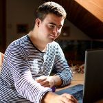 Young man with down syndrome using laptop indoors   tips to stay motivated in college