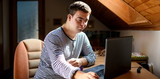 Young man with down syndrome using laptop indoors | tips to stay motivated in college
