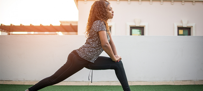 Black woman in fitness clothing doing lunge exercise | warm-up exercises