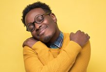 Black male hugging himself and smiling | benefits of self-compassion