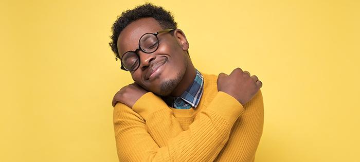 黑人男性拥抱自己和微笑,自我同情的好处