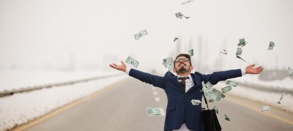 young man tossing cash in air