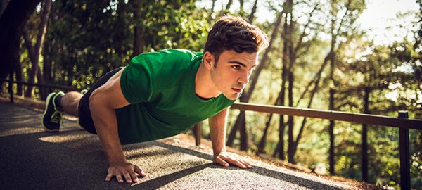 young man outdoors performing pushup circuits
