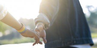 closeup LGBTQ couple holding hands in park | bi erasure