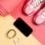 pink fitness equip and mobile device with earbuds on yellow background | fall fitness challenge