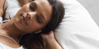 Middle eastern female relaxing in bed with headphones