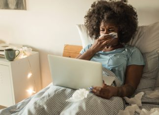 sick girl in bed looking at computer