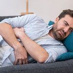 uncomfortable guy on couch   persistent bloating