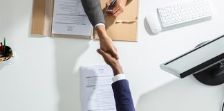 employer shaking hands with candidate over desk | how to build leadership skills