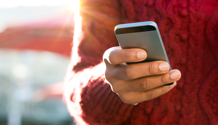 closeup of hand holding and dialing a phone