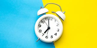 alarm clock on blue and yellow background