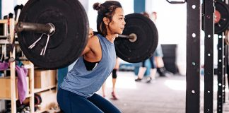 asian female squatting with barbell