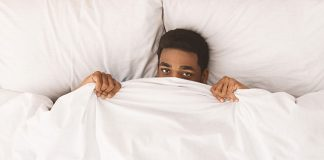 tired male in bed peeking over sheets