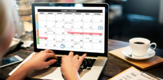 Overshoulder of someone working on laptop and a calendar is open on screen