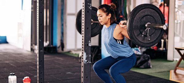 asian female training with squat rack