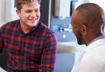 young man speaking with doctor