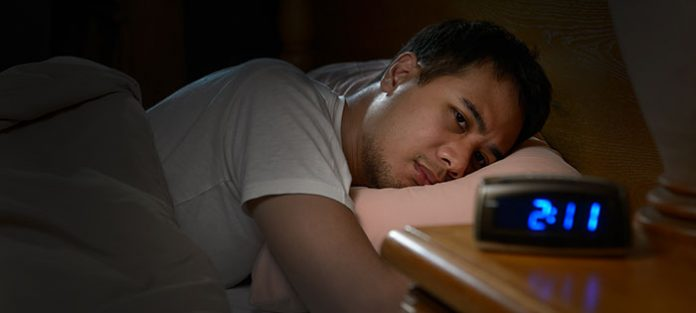 Guy awake in bed with clock reading