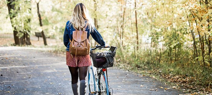 woman with backpack walking with bicycle