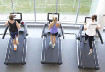 People-running-on-a-line-of-treadmills