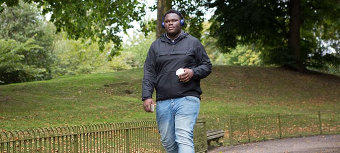 Guy walking through a park with headphones and a coffee